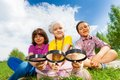 Three Kids Sitting Close Together With Magnifiers Stock Photo - 56447720