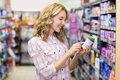 Side View Of Smiling Pretty Blonde Woman Looking At A Product Stock Photography - 56488172
