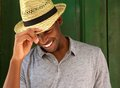Happy Young Man Laughing With Hat And Looking Down Royalty Free Stock Images - 56495709