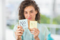 Smiling Businesswoman Holding Yes And No Sticks Stock Photography - 56496662