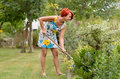 Adult Redhead Woman Raking The Flower Garden Royalty Free Stock Images - 56847749