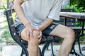 Man Holding Right Knee With Both Hands While Sitting Down Royalty Free Stock Image - 56851796