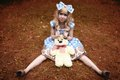 Happy Young Girl Sitting On Meadow With Teddy Bear In Summertime Dressed As Doll Royalty Free Stock Images - 56901769