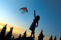Young Women Flying A Rainbow Kite Royalty Free Stock Images - 56905579