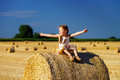 Funny Cute Little Girl Posing On The Haystack In Summer Field Royalty Free Stock Images - 57020749