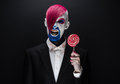Clown And Halloween Theme: Scary Clown With Pink Hair In A Black Jacket With Candy In Hand On A Dark Background In The Studio Stock Photo - 57093330