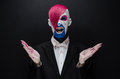 Clown And Halloween Theme: Scary Clown With Pink Hair In A Black Jacket With Candy In Hand On A Dark Background In The Studio Royalty Free Stock Photography - 57093657
