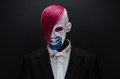 Clown And Halloween Theme: Scary Clown With Pink Hair In A Black Jacket With Candy In Hand On A Dark Background In The Studio Royalty Free Stock Photography - 57093777