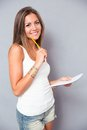Smiling Young Girl Holding Pencil And Notebook Stock Photography - 57184172