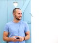 Smiling Man Listening To Music On Mobile Phone With Earphones Royalty Free Stock Photo - 57224265