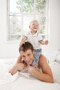 Young Father With His Nine Months Old Son On The Bed At Home Royalty Free Stock Photos - 57316588