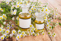 Herbal Medicine Concept - Bottle With Camomile On Wooden Table Stock Photo - 57356580