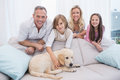 Puppy Lying On The Couch With The Family Standing Behind Royalty Free Stock Photo - 57364865