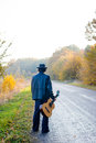 Lonely Guitarist Looking At Empty Country Road In Stock Photo - 57393610