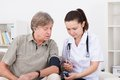 Doctor Measuring Blood Pressure Of Patient Stock Photos - 57432473