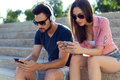 Two Friends Using Mobile Phone And Listening To Music In The Str Royalty Free Stock Photos - 57491028