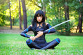 Young Girl Sitting On The Grass And Holding Samurai Sword. Royalty Free Stock Photo - 57555095