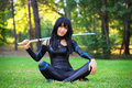 Young Girl Sitting On The Grass And Holding Samurai Sword. Stock Image - 57555121