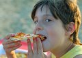 Boy Eats Pizza With Potato Chips On The Beach Royalty Free Stock Photography - 57579547