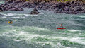 Kayakers Navigating Through The White Water Rapids And Around Rocks Royalty Free Stock Images - 57686709