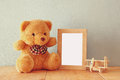 Wooden Airplane Toy And Teddy Bear Over Wood Table Next To Blank Photo Frame. Retro Filtered Image. Ready To Place Photography Royalty Free Stock Photo - 57804975