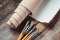 Artist Canvas In Roll And Paintbrushes On Table Stock Photo - 57841890