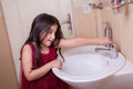 One Beautiful Little Middle Eastern Arab Girl With Red Dress Is Washing Her Hands In The Bathroom. Royalty Free Stock Image - 57870516