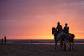 Two Mounted Guardia Civil Police Officers Patrolling Beach At Sunset Stock Photography - 57905852