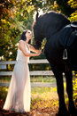 Fashionable Lady With White Bridal Dress Near Brown Horse In Nature. Beautiful Young Woman In A Long Dress Posing With A Horse Stock Photos - 58036753
