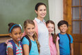 Teacher And Pupils Smiling In Classroom Royalty Free Stock Images - 58136129