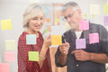 Business Team Pointing Post Its On The Wall Stock Images - 58184824