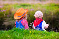 Little Boy And Girl Dressed Up As Cowboy And Cowgirl Playing Wit Royalty Free Stock Image - 58226646