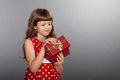 Little Girl In Red Dress Holding Her Present Stock Photography - 58265742