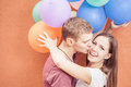 Young Happy Couple Near The Orange Wall Stand With Balloons Stock Photo - 58272890