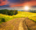 Road On Hillside Meadow In Mountain At Sunset Royalty Free Stock Photos - 58341308