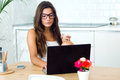 Beautiful Young Woman Using Her Laptop Amb Drinking Coffee At Ho Royalty Free Stock Images - 58518389