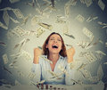 Woman Sitting At Table With Growing Stack Of Coins Under A Money Rain Stock Photo - 58533800