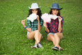 Beautiful Girls In Cowboy Hats Eating Cotton Candy Royalty Free Stock Images - 58557559