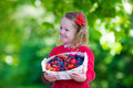 Little Girl With Fresh Berries In A Basket Royalty Free Stock Photos - 58581388
