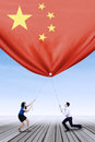 Entrepreneurs Pulling Down A Chinese Flag Royalty Free Stock Image - 58602126