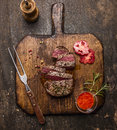 Roasted  Ribeye Steak Sliced ​​on A Cutting Board With A Fork, Red Sauce, Peppers And Tomatoes On Rustic Wooden Background, Royalty Free Stock Image - 58626526