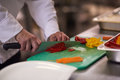 Chef In Hotel Kitchen  Slice  Vegetables With Knife Royalty Free Stock Photos - 58634198