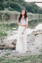 Beautiful Woman With Long Curly Hair Dressed In Boho Style Dress Posing Near Lake Stock Photos - 58695933