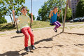 Two Happy Kids Swinging On Swing At Playground Stock Photos - 58762533