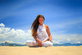 Girl In Lace In Yoga Asana Lotus On Beach Against Blue Sky Stock Photos - 58781433