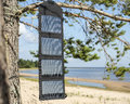 Portable Foldable Solar Panel Battery Hanging On The Outdoors On A Pine Tree Stock Photos - 58790963