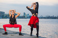 Two Young Beautiful Twin Sisters Are Dancing Waacking Dance In The City Background Near River. Royalty Free Stock Photos - 58794138