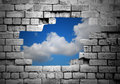Hole In Brick Wall Revealing Clouds Royalty Free Stock Image - 58866506