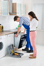Woman Looking At Male Worker Repairing Oven Stock Photo - 58875180