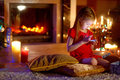 Happy Little Girl Playing With Her Smart Phone On Christmas Eve Royalty Free Stock Photo - 58944165
